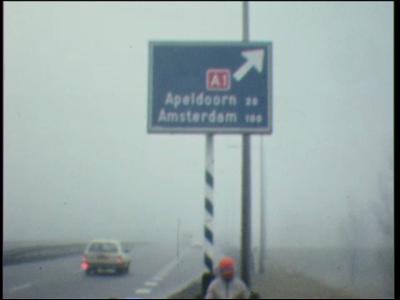 5045 BB07735 Een film waarin een man, voorzien van helm, langs een snelweg op een stoel zit voor een ANWB-bord (A1 ...