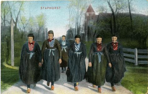 1420 PBKR6082 Ingekleurde prentbriefkaart van vrouwen in klederdracht, met op de achtergrond de Hervormde Kerk uit ...