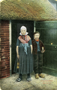 2234 PBKR5638 Merisje en jongen in klederdracht bij een staldeur, beiden met een kerkboek of bijbel in de bhand. DDe ...
