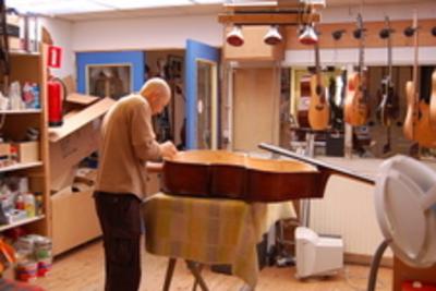 Ferdinand Rikkers : reparatie van een contrabas in zijn werkplaats aan de Rijksweg 13