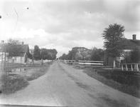 Weg met lintbebouwing, op de achtergrond is een brug zichtbaar